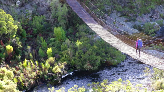 Female hiker walks over wooden swing bridge
