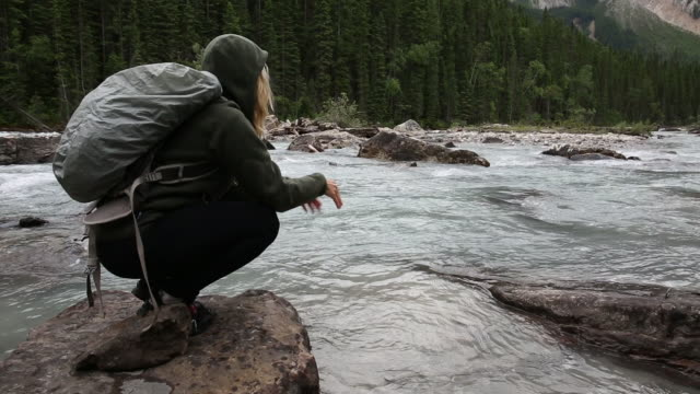 Female hiker walks to river's edge, bends down to test water