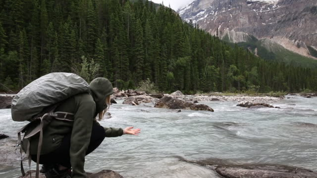 female hiker walks to river's edge, bends down to test water - one mature woman only stock videos & royalty-free footage