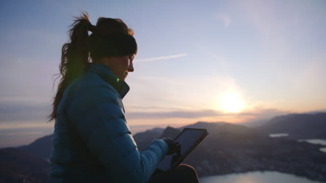 female hiker works on digital tablet overlooking mountains and lake below - accessibility stock videos & royalty-free footage