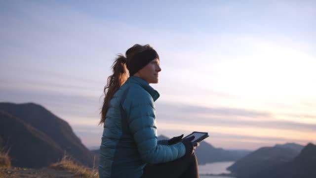 weibliche wandererarbeitet auf digitalem tablet mit blick auf berge und see unten - mobilität stock-videos und b-roll-filmmaterial