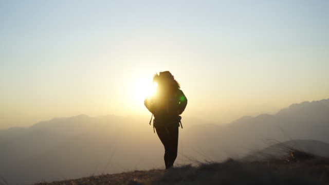 日没時に山の尾根に沿って女性のハイキング、彼女の後ろの山の眺め - 方向点の映像素材/bロール