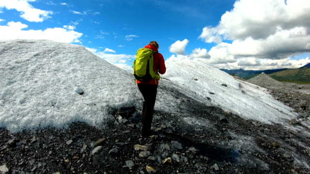 pov female hiking moraine covered melting snow alaska - pacific war stock-videos und b-roll-filmmaterial