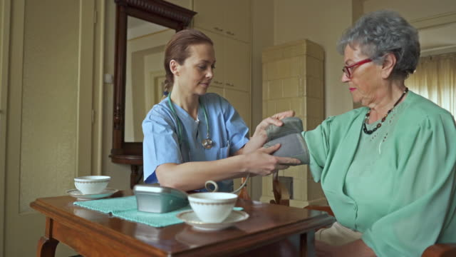 Female home caregiver measuring blood pressure of an old woman.