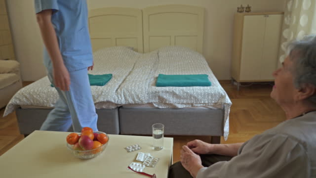 female home caregiver visiting old woman and talking to her about prescription medicines. - female nurse stock videos and b-roll footage