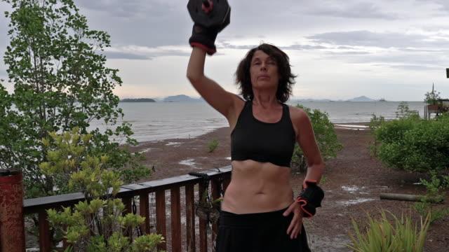 stockvideo's en b-roll-footage met vrouwelijke home oefening dumbell druk gewichtsverlies transformatie - one mature woman only