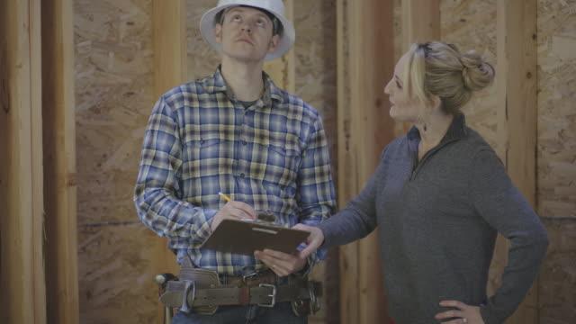 vidéos et rushes de femme propriétaire d'une maison passant par des plans de construction avec un entrepreneur de construction générale - âges mélangés