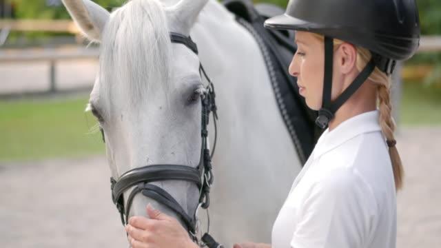 stockvideo's en b-roll-footage met slo mo vrouwelijke ruiter aaien van haar witte paard op de neus - alleen één mid volwassen vrouw