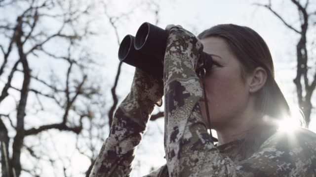 female hunter looks through binoculars, close up - 迷彩柄点の映像素材/bロール