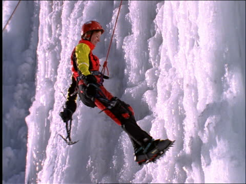 female ice climber rappelling down icy cliff face - face down stock videos & royalty-free footage