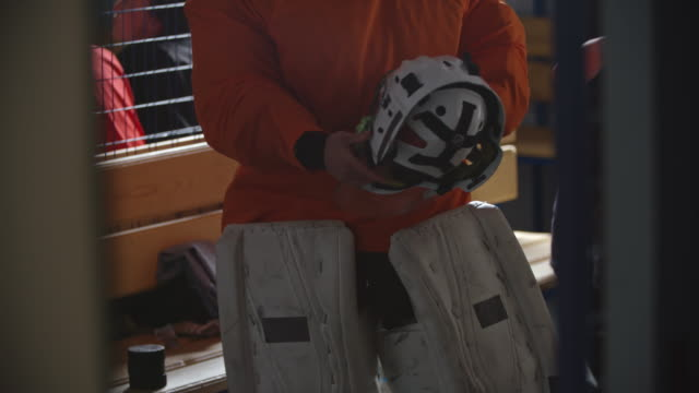 female ice hockey goalie putting protective helmet on - leanincollection stock videos & royalty-free footage