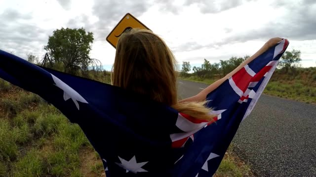 female in australia holding flag near kangaroo sign - road warning sign stock videos & royalty-free footage