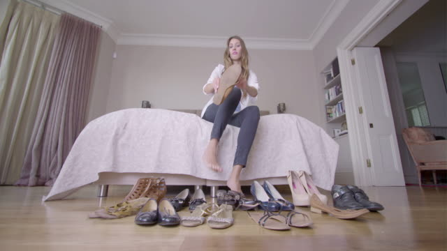 Female in bedroom choosing shoe to wear