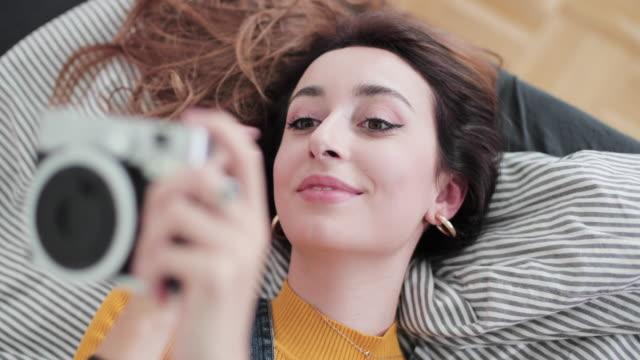 vídeos y material grabado en eventos de stock de female in bedroom looking at images on camera - de origen español o portugués