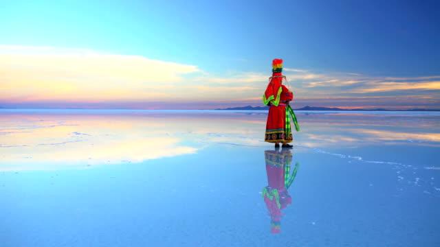 female in bolivian national traditional dress at sunrise - ウユニ塩湖点の映像素材/bロール