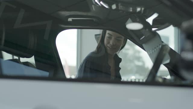 vídeos y material grabado en eventos de stock de female in car showroom looking at new electric car trough window at automotive dealership - new