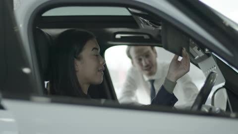 vídeos y material grabado en eventos de stock de female in car showroom talking to sales person and looking at automotive vehicle in dealership - coche eléctrico coche alternativo