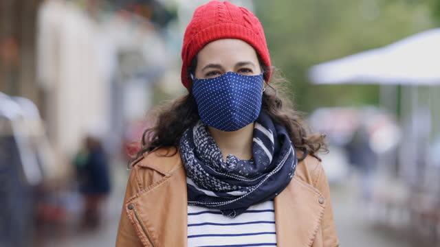 stockvideo's en b-roll-footage met vrouw in gezichtsmasker op voetpad in stad - muts