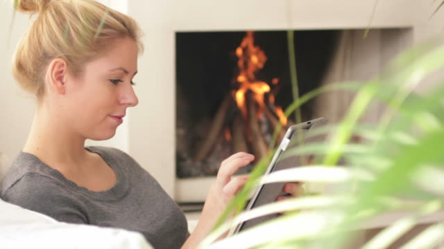Female in front of fireplace looking at digital tablet