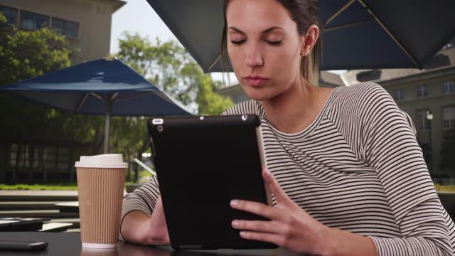 female in her 20s with coffee using pad device sitting outside on college campus - istruzione post secondaria video stock e b–roll