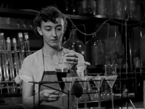 vídeos y material grabado en eventos de stock de female in laboratory behind counter w/ dark liquid in lab funnel, measuring small amount of dark liquid out, pouring dark liquid out of beaker onto... - 1952