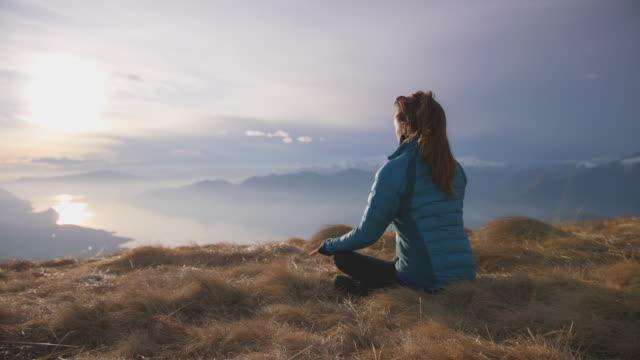 female in meditating pose on mountain top enjoying view of sunset - mountain pose stock videos & royalty-free footage