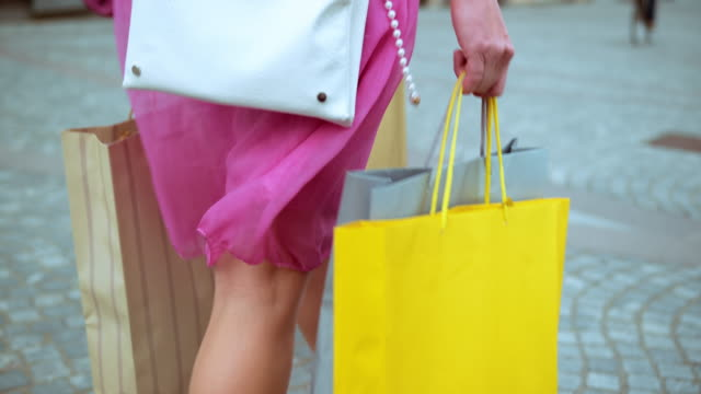 slo mo female in pink dress walking with shopping bags - consumerism stock videos and b-roll footage