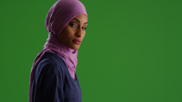 stockvideo's en b-roll-footage met female in purple headscarf looking at camera on green screen - hoofddoek
