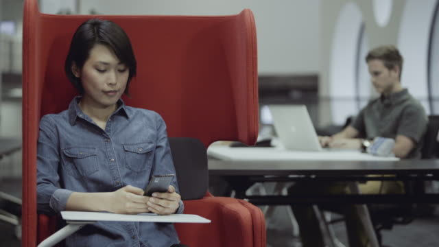 stockvideo's en b-roll-footage met female in red chair on mobile smart phone - werkneemster
