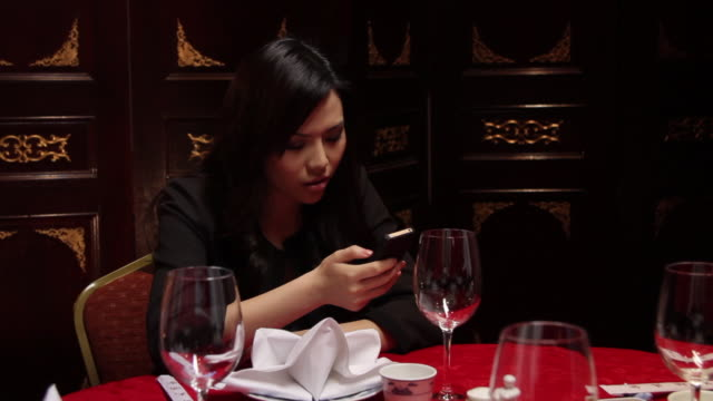 female in restaurant looking at mobile whilst waiting for date - foodie stock videos and b-roll footage