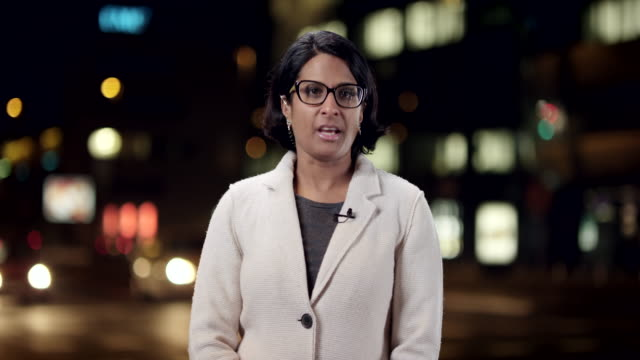female indian correspondent reporting live to the studio from the city center at night - tv reporter stock videos & royalty-free footage
