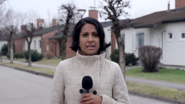 female indian on the scene reporter talking and holding a microphone in her hand - tv reporter stock videos & royalty-free footage