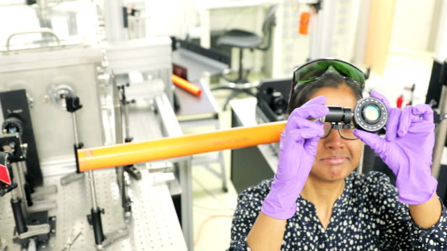 Female Indian Researcher Cleaning Lens of a High Frequency Laser in Laboratory