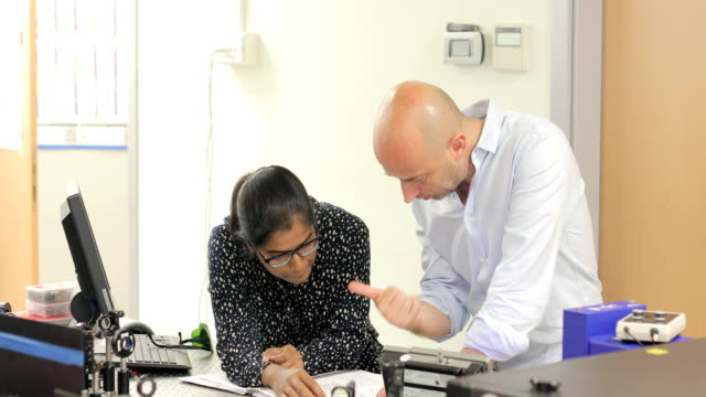 female indian student having a discussion with a professor in laboratory - centro di ricerca video stock e b–roll