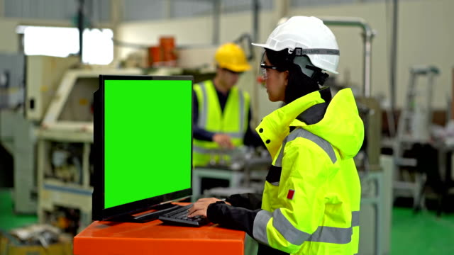vídeos de stock e filmes b-roll de female industrial engineer using a computer with green screen monitor working in a heavy industry manufacturing factory - maquinaria de fabrico
