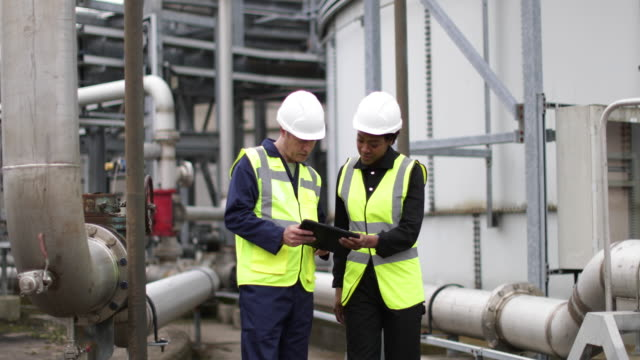 vidéos et rushes de female industrial worker being trained using a digital tablet on site - industrie du pétrole