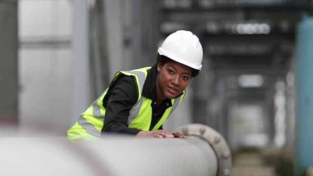 female industrial worker checking pipeline - oil refinery stock videos & royalty-free footage