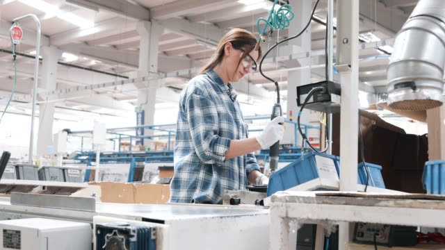 Female industrial worker using air impact wrenches at factory
