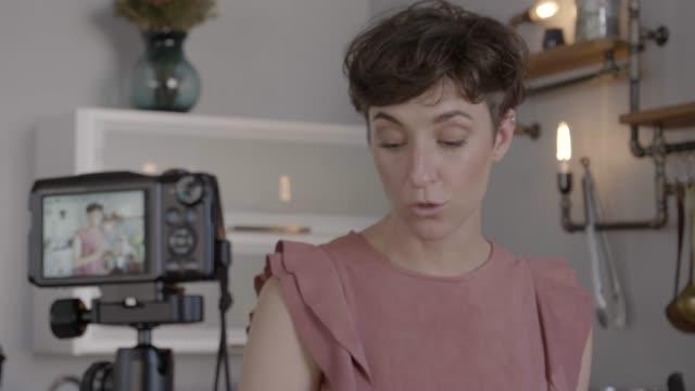 vidéos et rushes de female influencer making video in kitchen - services sociaux
