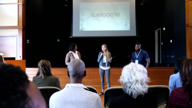 female influencer welcomes crowd to seminar - lectern stock videos & royalty-free footage