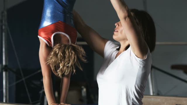 vídeos de stock e filmes b-roll de ms td tu female instructor assisting girl (8-9) exercising on balance bar in gym, orem, utah, usa - leotard