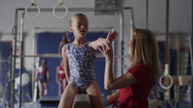 ms female instructor assisting girl (10-11) exercising on balance beam, orem, utah, usa - orem utah stock videos & royalty-free footage
