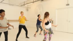Female instructor teaching dance to students