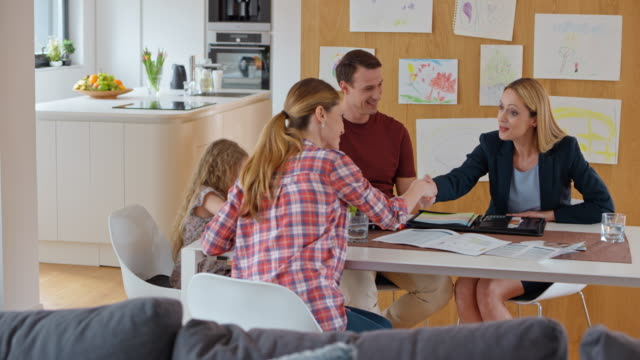 Female insurance agent shaking hands with a couple at a meeting in their house