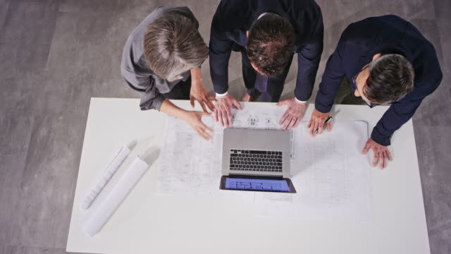 cs female interior and her male colleague architect explaining the design of the space on the laptop to the male investor - beginnings stock videos & royalty-free footage
