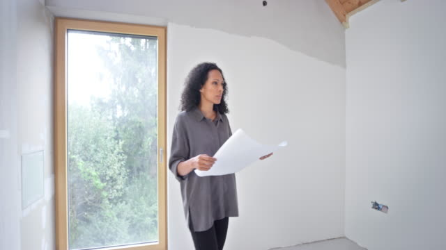 female interior architect holding plans while walking in the building - tracking shot stock videos & royalty-free footage