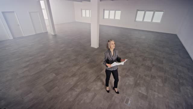 cs innenarchitektin schaut sich die pläne an, die über den leeren büroraum gehen - in den vierzigern stock-videos und b-roll-filmmaterial
