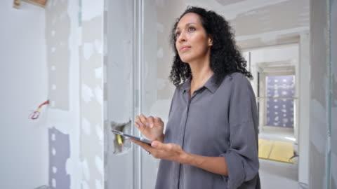 vidéos et rushes de architecte d'intérieur féminin marchant à l'intérieur du bâtiment en construction avec une tablette numérique dans sa main - lotissement