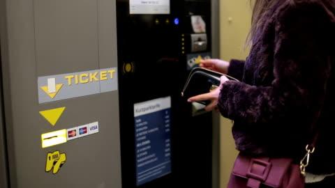 vídeos y material grabado en eventos de stock de mujer compra un ticket de aparcamiento en una máquina con una tarjeta de crédito - aparcamiento
