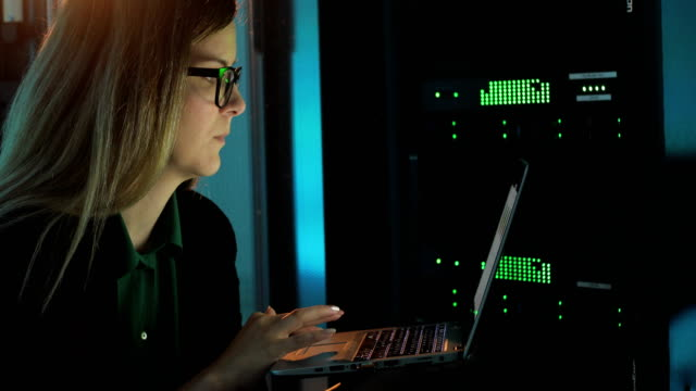 Female IT Engineer Checking on Super Computer with her Laptop